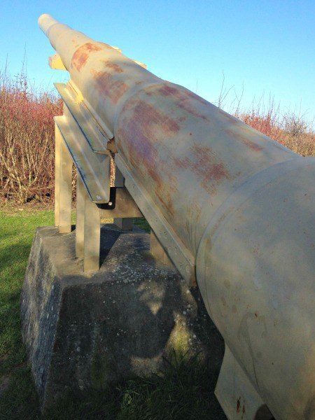 A rusted canon sits the way it would have been positioned during WWII.