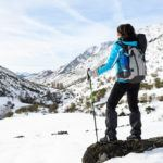 Woman hiking on winter snowy mountains. Hiker looking nature landscape on winter vacations travel.