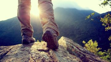 Gifts for Hikers: woman hiker legs stand on mountain peak rock