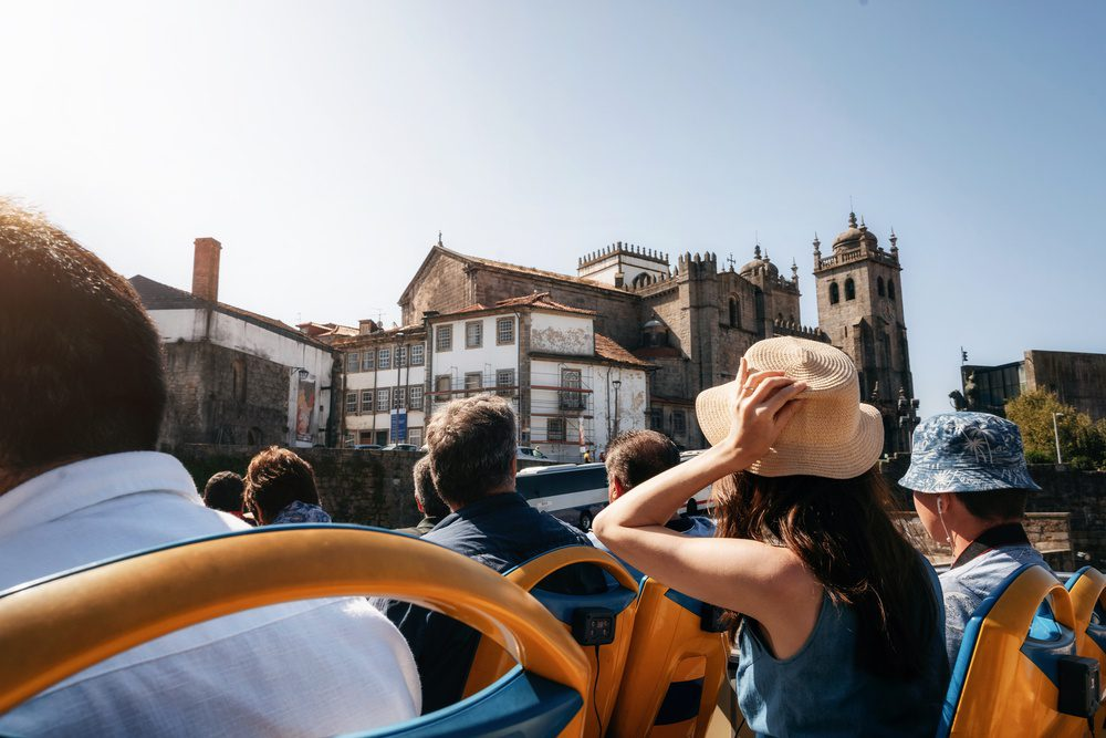 Tourists on open top sightseeing bus in city